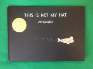 Photograph of Front Cover of This Is Not My Hat shows a little fish wearing a bowler hat swimming away on a black background