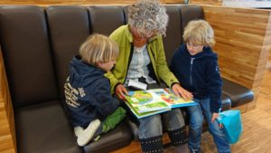 photograph of a grandmother reading to her two grandchildren